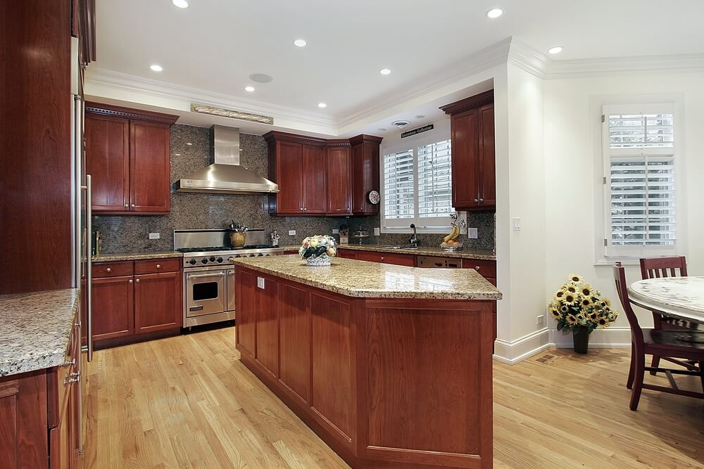 This Kitchen Features Matching Countertops And Backsplash As Well Set Against Cherry Wood Cabinets