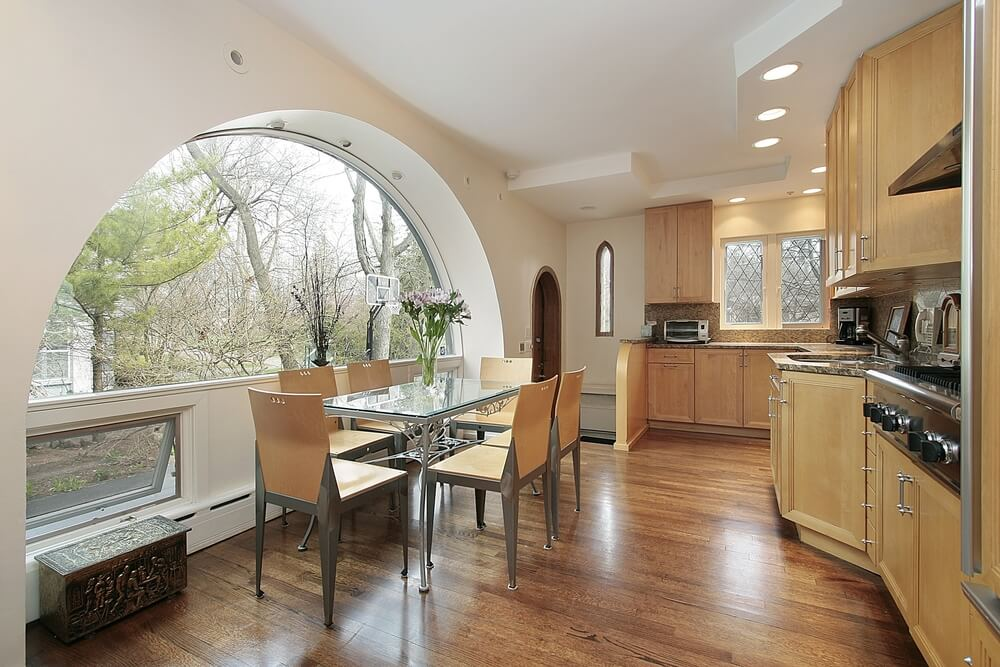 Here we have an example of open kitchen design with light wood keeping up in brightness with the large open window.
