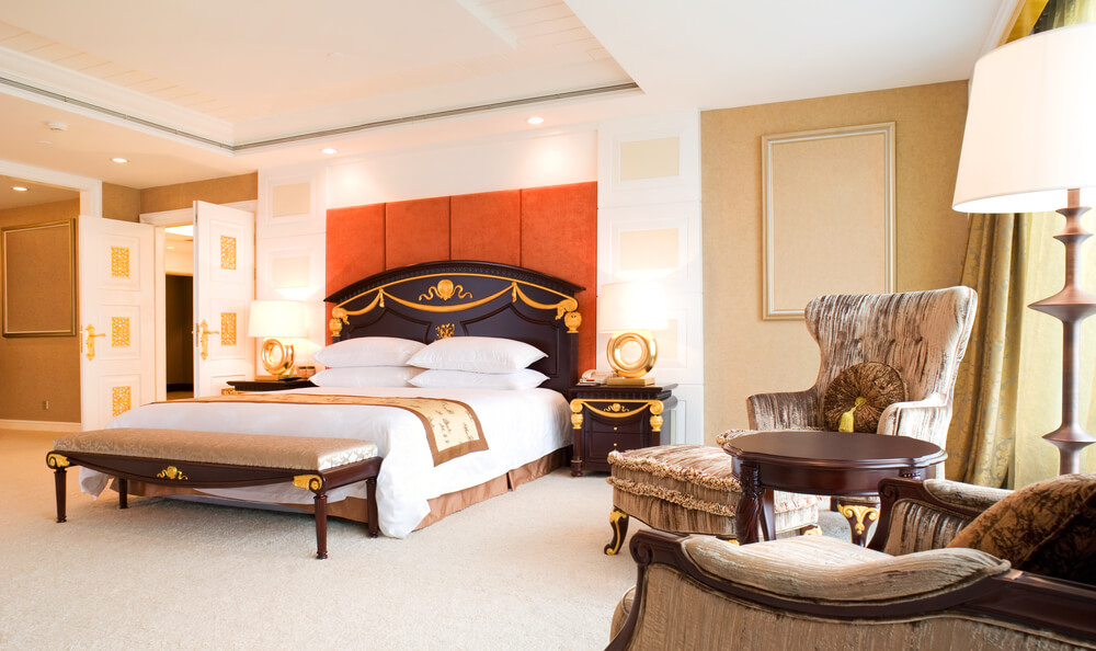 Bright white and gold hotel room highlighted with bold orange wall behind filigreed head board.