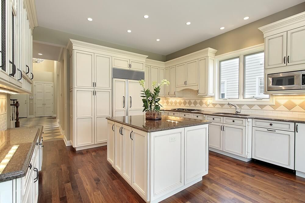 White Cupboards Surround This Kitchen, Featuring Patterned Tile Backsplash  And Hardwood Flooring.