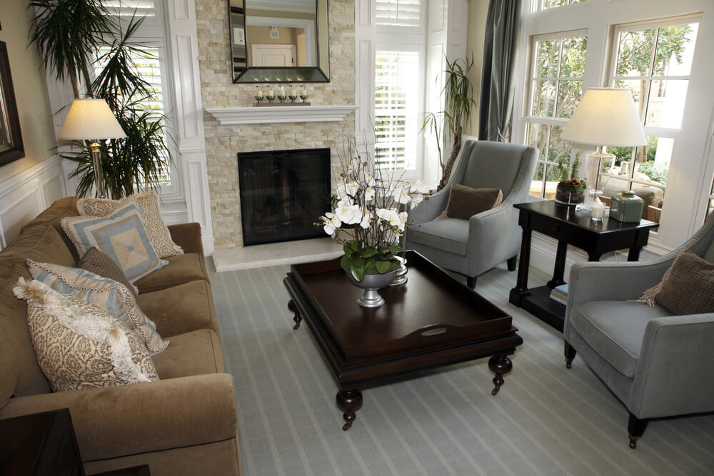 Traditional living room design with ornate dark wood coffee table, two blue- grey armchairs