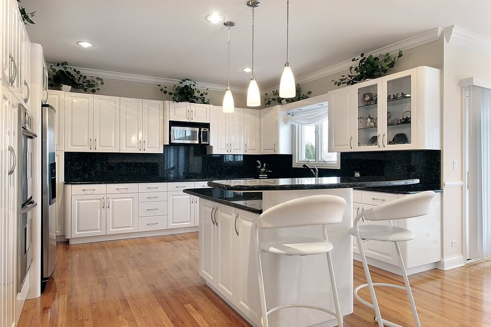 Another White Kitchen Accented With Black Countertops, Plus Black  Backsplash And Hardwood Flooring.