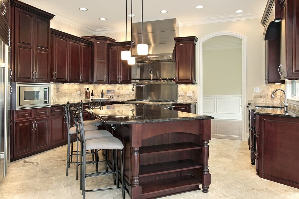 Imposing Dark Wood Island With Black Countertop Dominates This Kitchen  Featuring Brushed Aluminum Appliances.