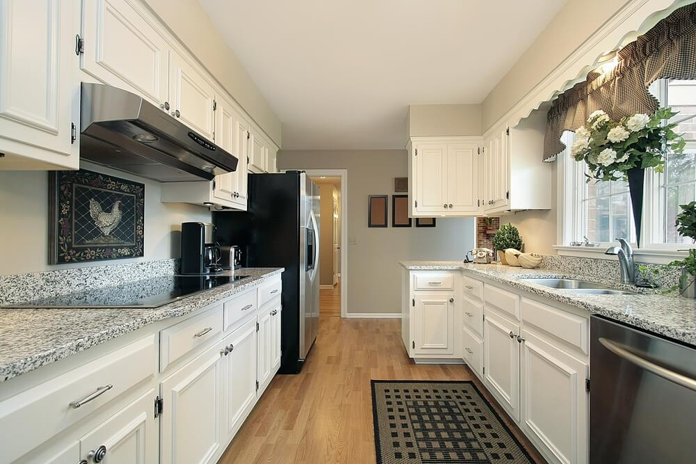 Long Narrow Kitchen Features White Cupboards And Light Colored Wall Paint Along With Aluminum