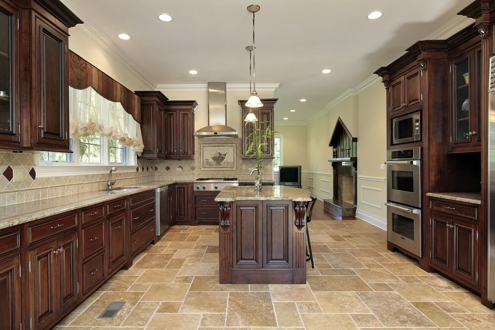 Stately Cabinet Design In This Kitchen Is Strengthened By Dark Wood Over The Light Tile Flooring