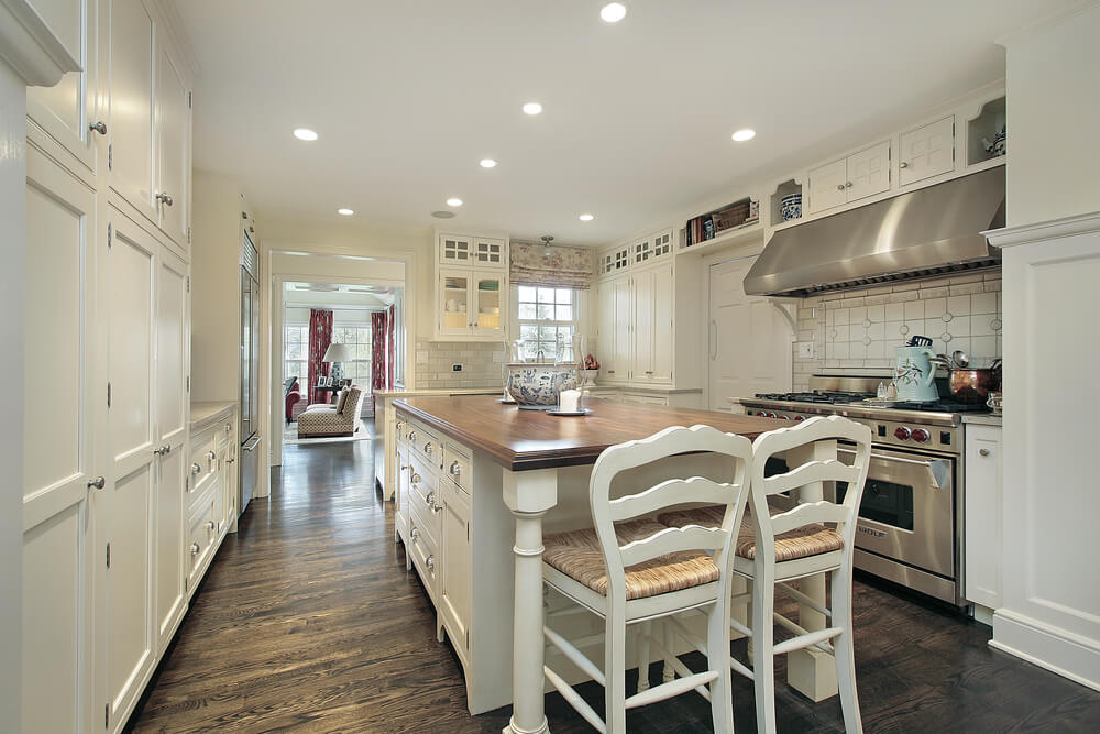White Kitchen Features Extensive Shelving Dual Brushed Aluminum Ovens And Large Central Island With
