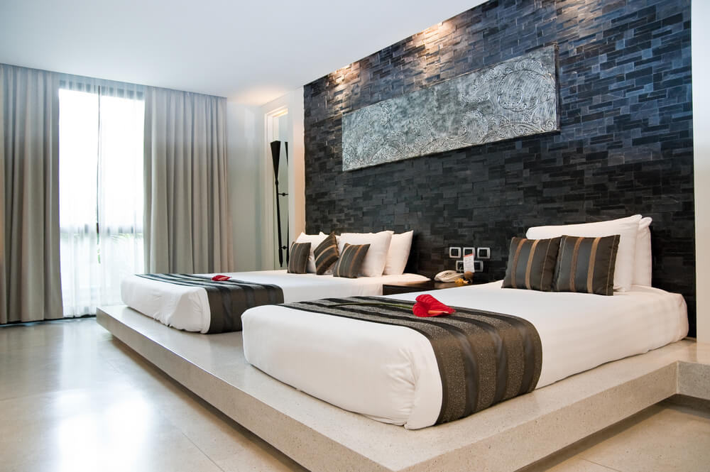 Dark brick patterned wall with sculpted art piece at center commands attention in this white, minimal room featuring two beds on a single raised platform.