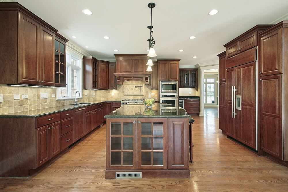 Light Hardwood Flooring And Dark Wooden Cabinetry Compliment Each Other In This Kitchen Featuring Tile