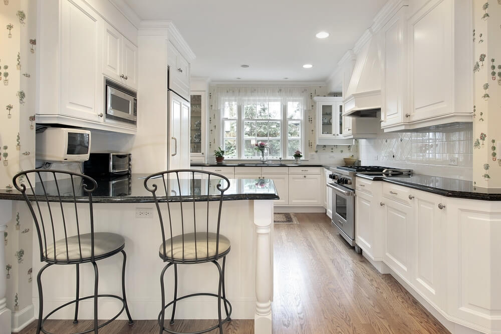 All White Kitchen Accented With Black Countertops And Wrought Iron Chairs Plus Natural Wood
