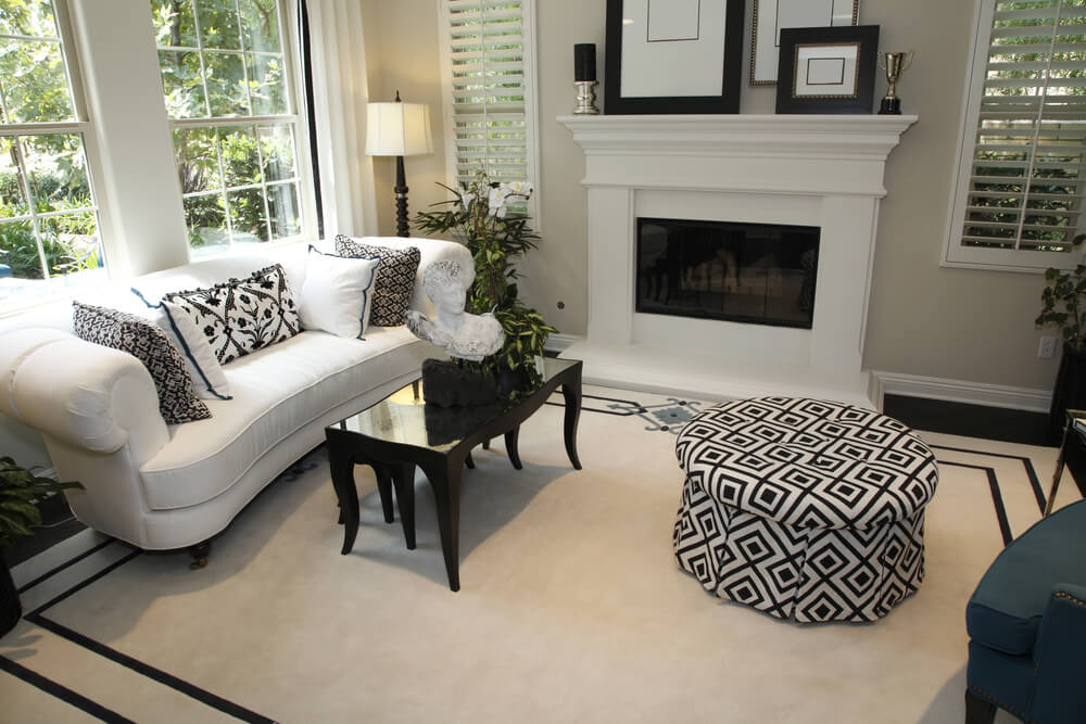 Small Living Room Mainly In White With A Black And White Patterned Round  Ottoman And Sofa