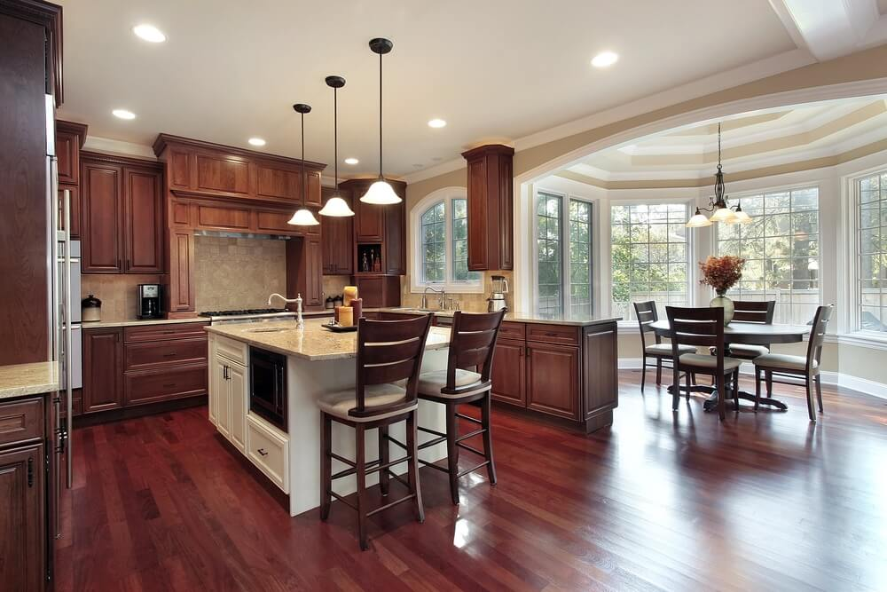 Cherry Wood Flooring And Natural Toned Wood Cabinetry Warm Up This Kitchen,  Featuring Attached Dining