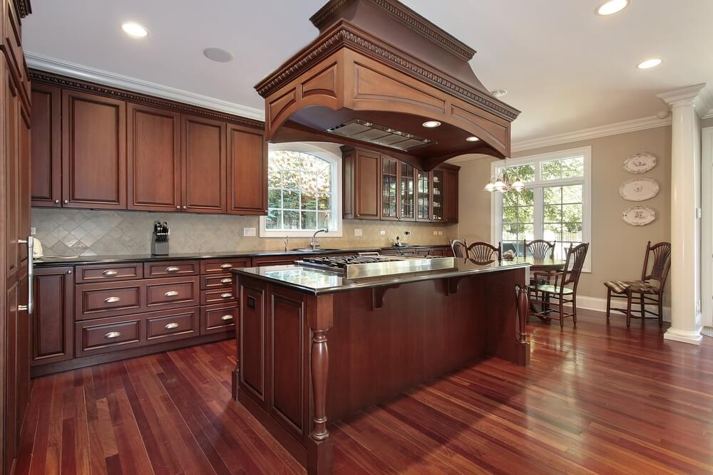 Rich Wood Abounds In This Kitchen Featuring A Massive Island With Built In  Range,