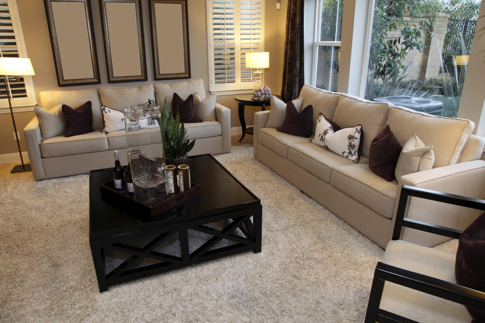 Living Room Design With One Dominant Color Being Beige Offset With A Dark  Wood Coffee Table