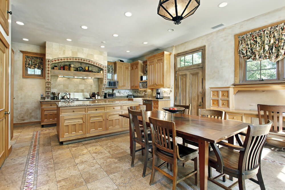 This old fashioned tile floor kitchen's wide open design is complimented by light wood cabinetry and marble topped island.