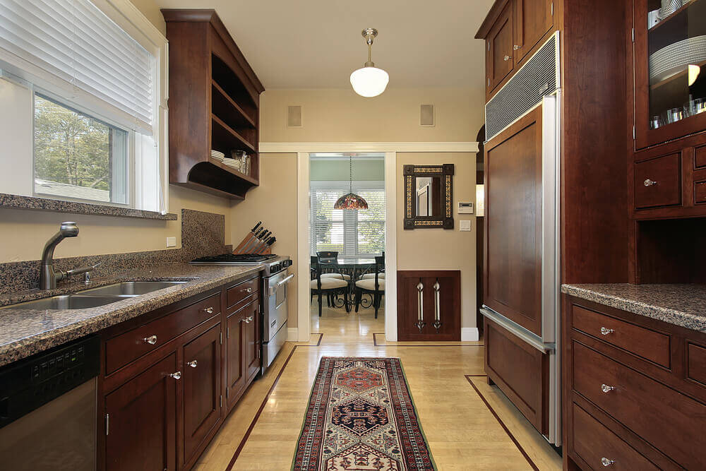 Dark Wood Cabinetry Surrounds In This Kitchen, Featuring On The  Refrigerator.