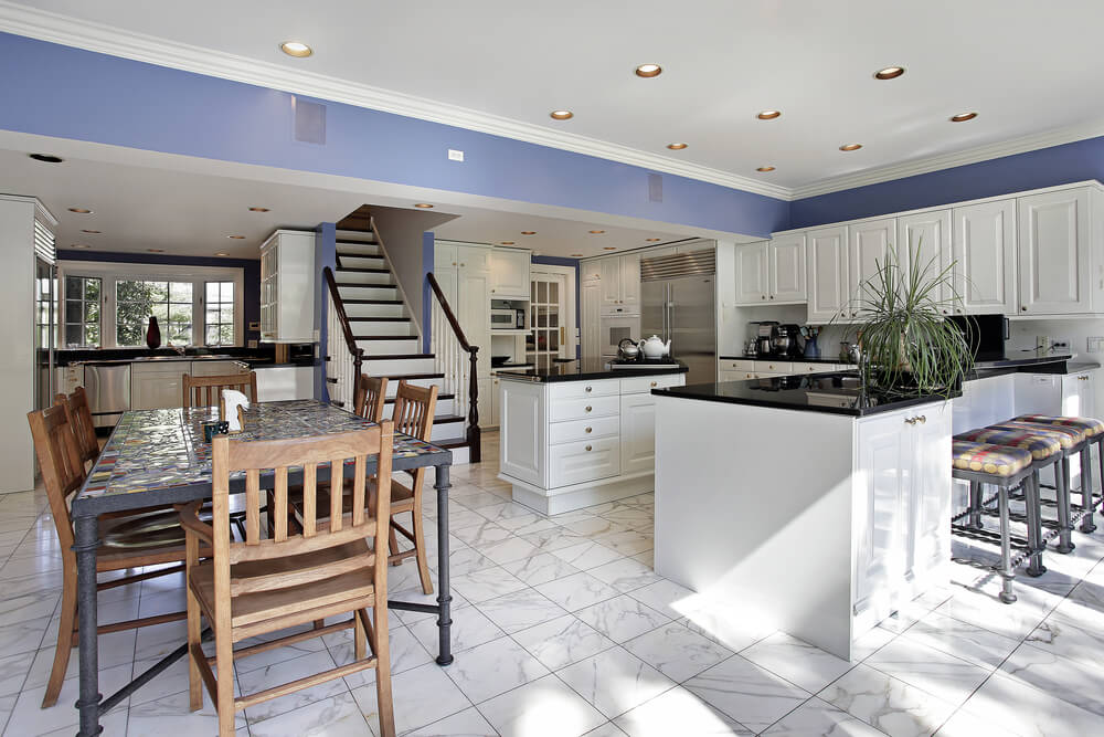 Sprawling White Kitchen Featuring Open Design Black Countertops Blue Wall Accent And Central