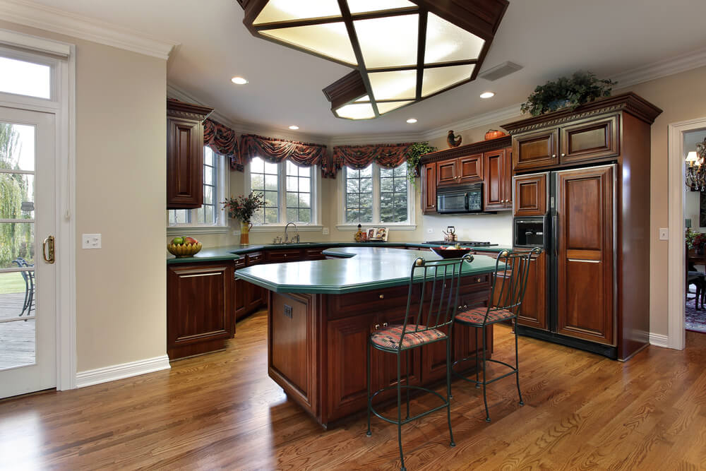 Natural hardwood flooring in this kitchen anchors the room, with unique cross-hatch lighting design and forest green countertops.