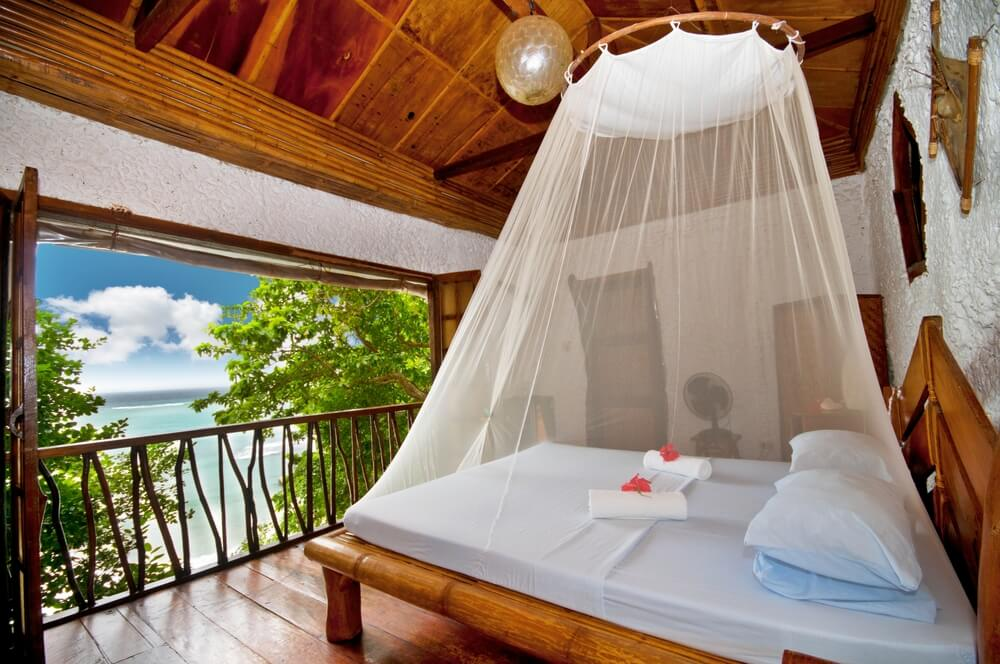 Here's another tropical styled room, featuring bamboo bed frame, ceiling arches, and enormous balcony opening.
