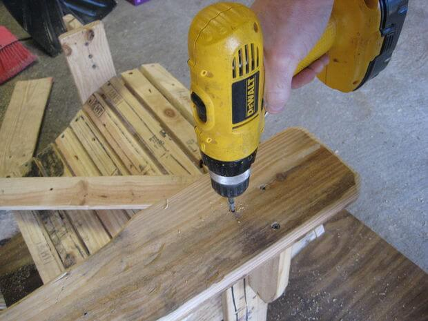 Drilling screws to attach the Adirondack chair's armrest