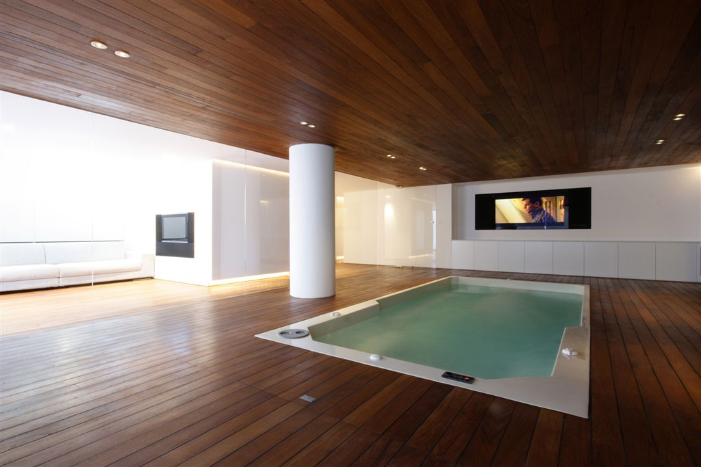 Angled view of pool room, featuring another media strip with embedded TV on far wall.