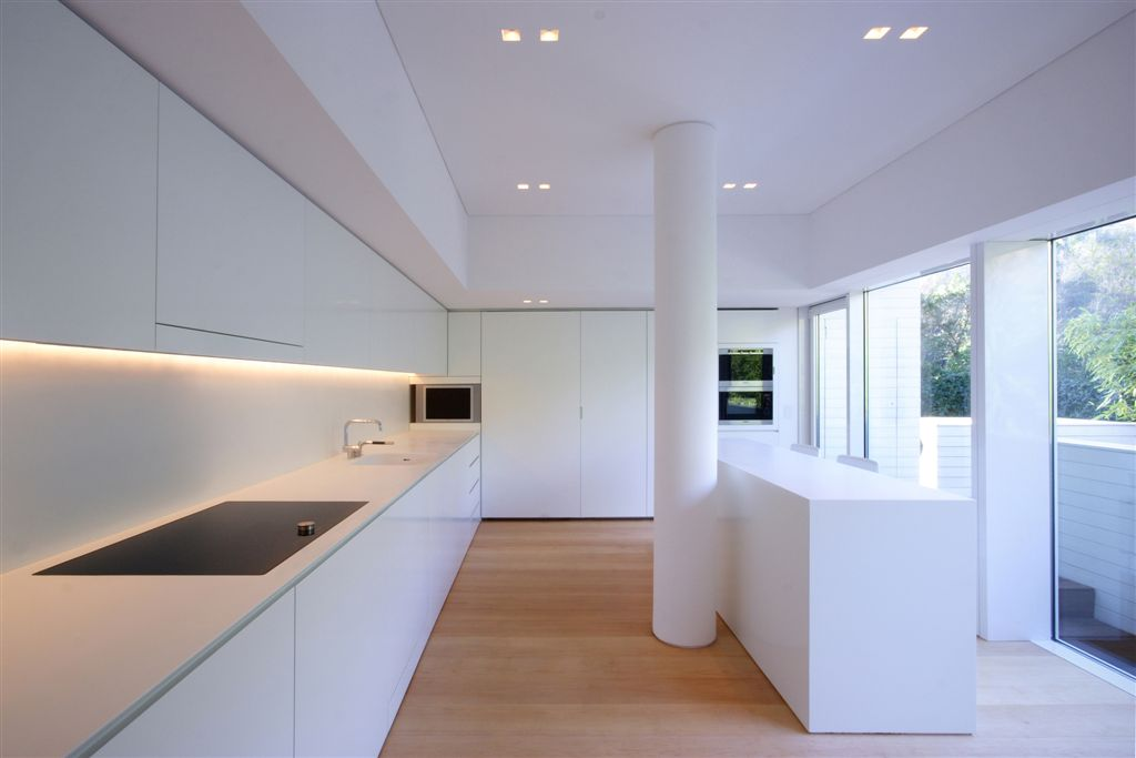 Kitchen area centered around white pillar, with bar style seating and view through glass wall to outdoor area.