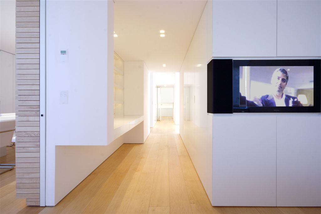 Central hallway connecting all rooms, replete with white on all vertical surfaces and small media strip echoing the living room.