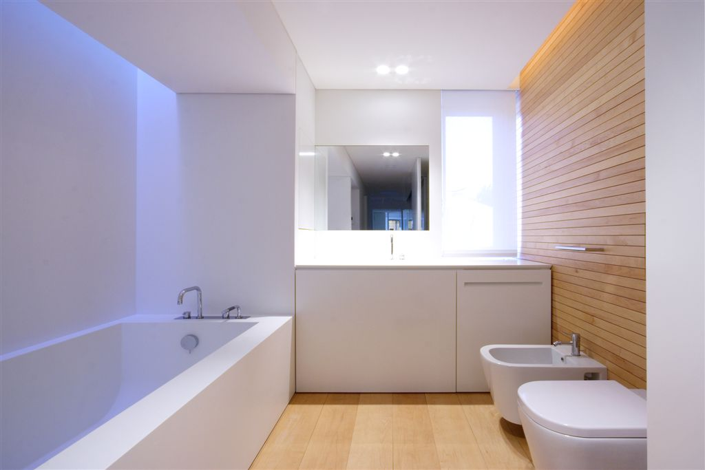 Ultra modern bathroom featuring large bath matching all white interior.