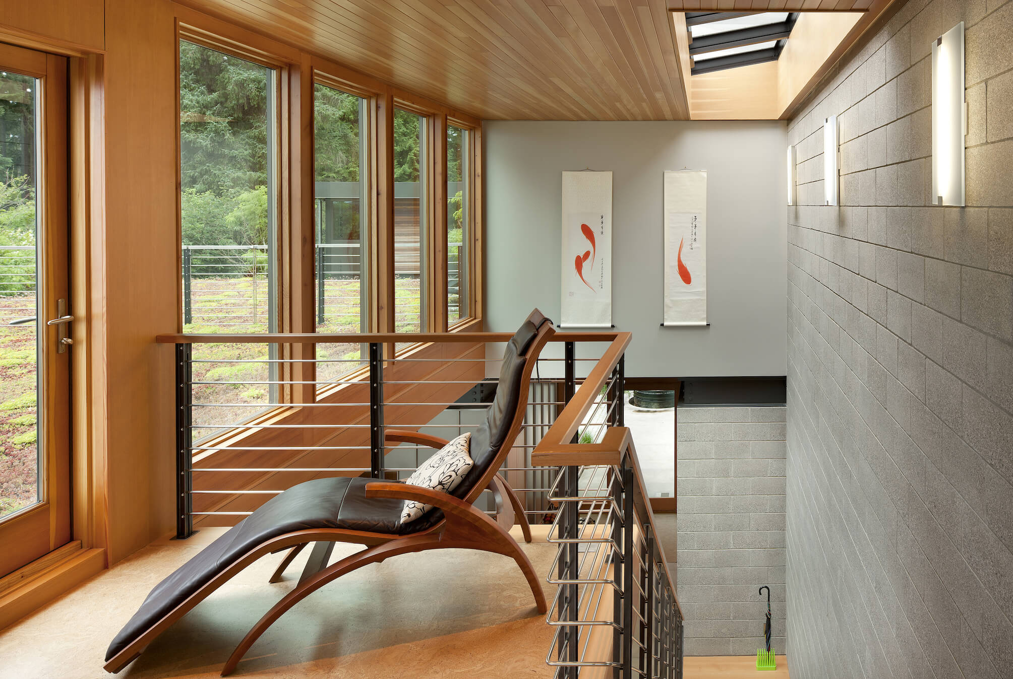 Landing atop staircase featuring wood and metal rail, curved wood and leather chaise lounge and patio door set in natural wood wall with windows all around.