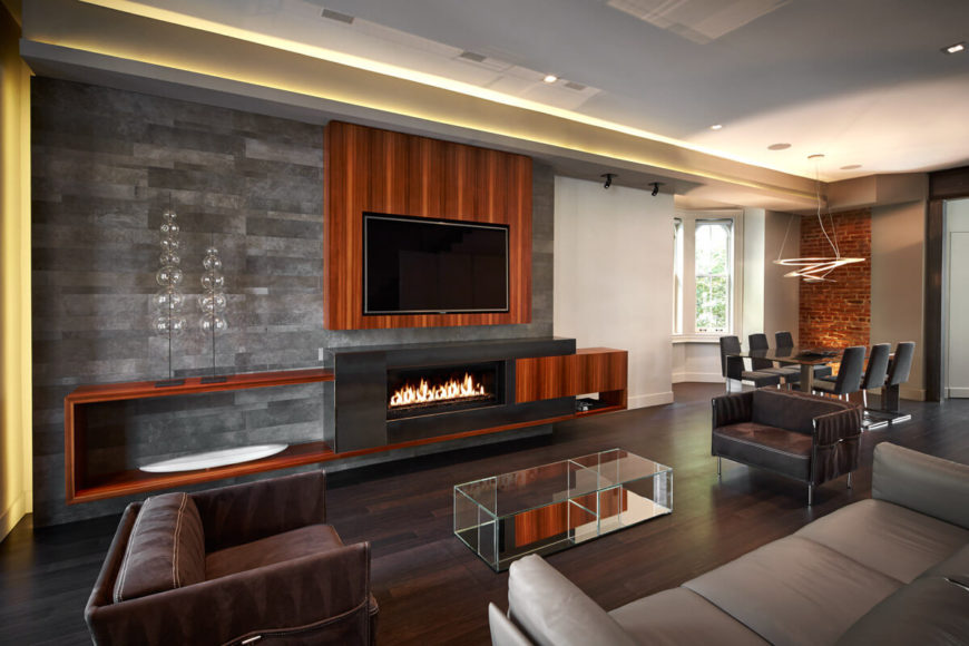 This is a more direct shot of the living room, showcasing the bright natural wood tones on wall supporting mounted television, with gas fireplace built into metal and wood shelving. Dining area is seen in background, with leather furniture up close.