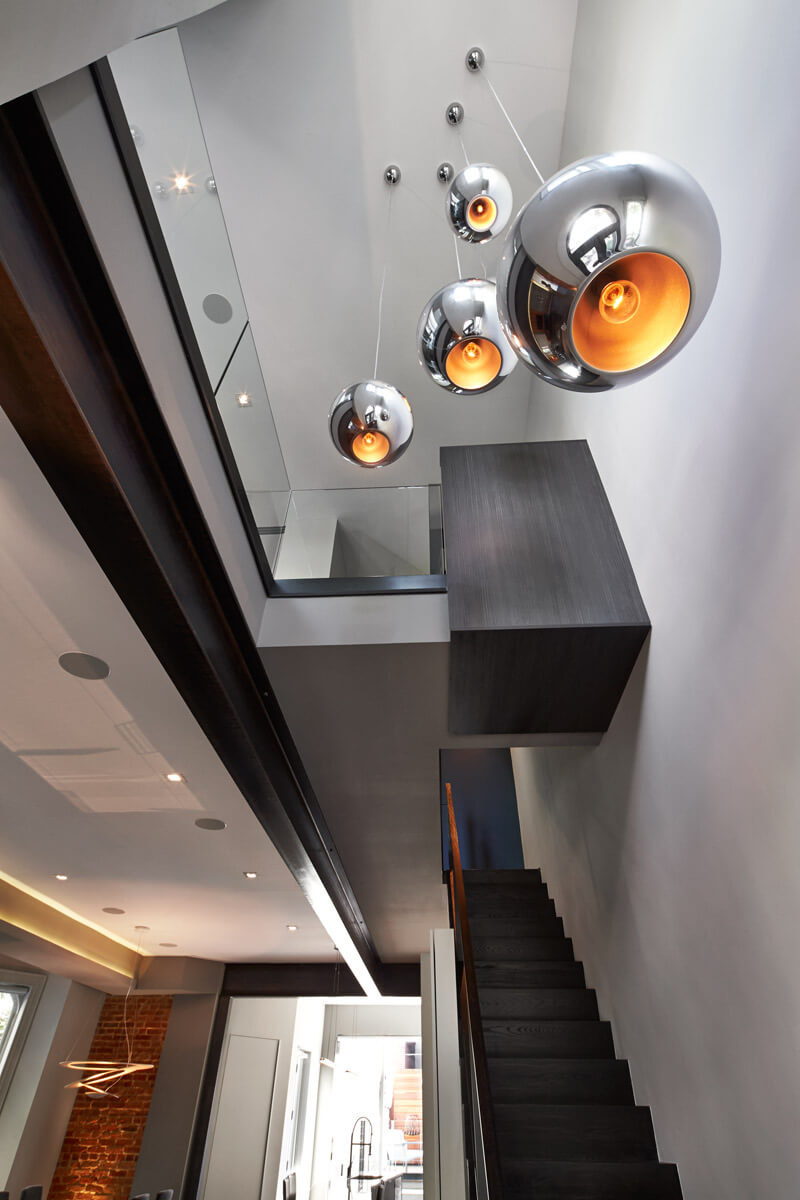 Upward facing view of black wood staircase, lit with hung chrome spherical chandeliers over entryway. Glass walls separate upstairs area.
