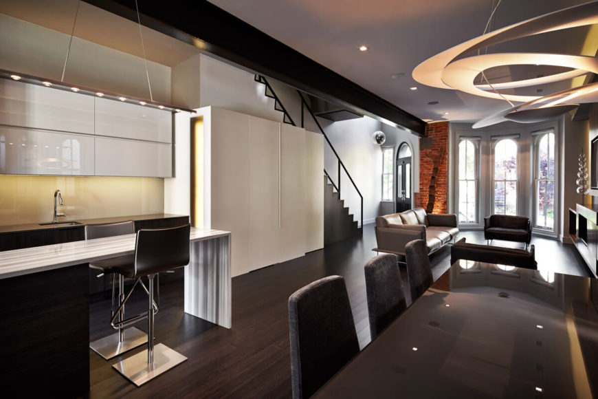 The dining area fills in the open space between kitchen and living room, with unique ringed chandelier over reflective dark tabletop. Bold white panels are seen next to staircase, with living room in background.