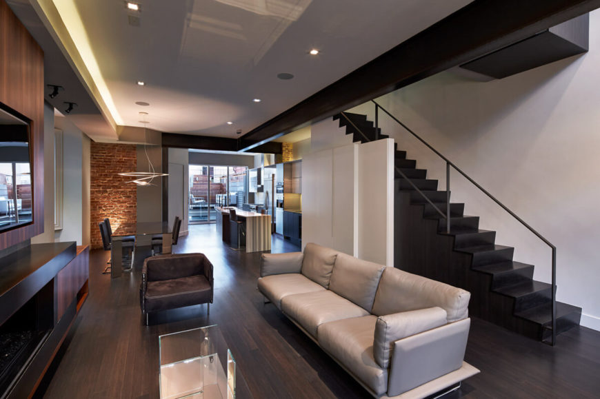 Here's the opposite angle of the shared space including living room, dining, and kitchen areas. Black staircase prominently contrasts with natural hardwood flooring and white walls and cabinetry. Light and dark leather seating surround mirrored glass coffee table.