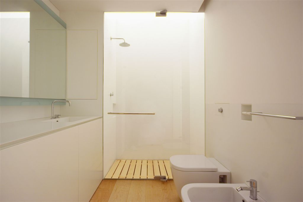 Second bathroom showcasing all-white design with natural hardwood flooring, minimalist angles, and glass shower.