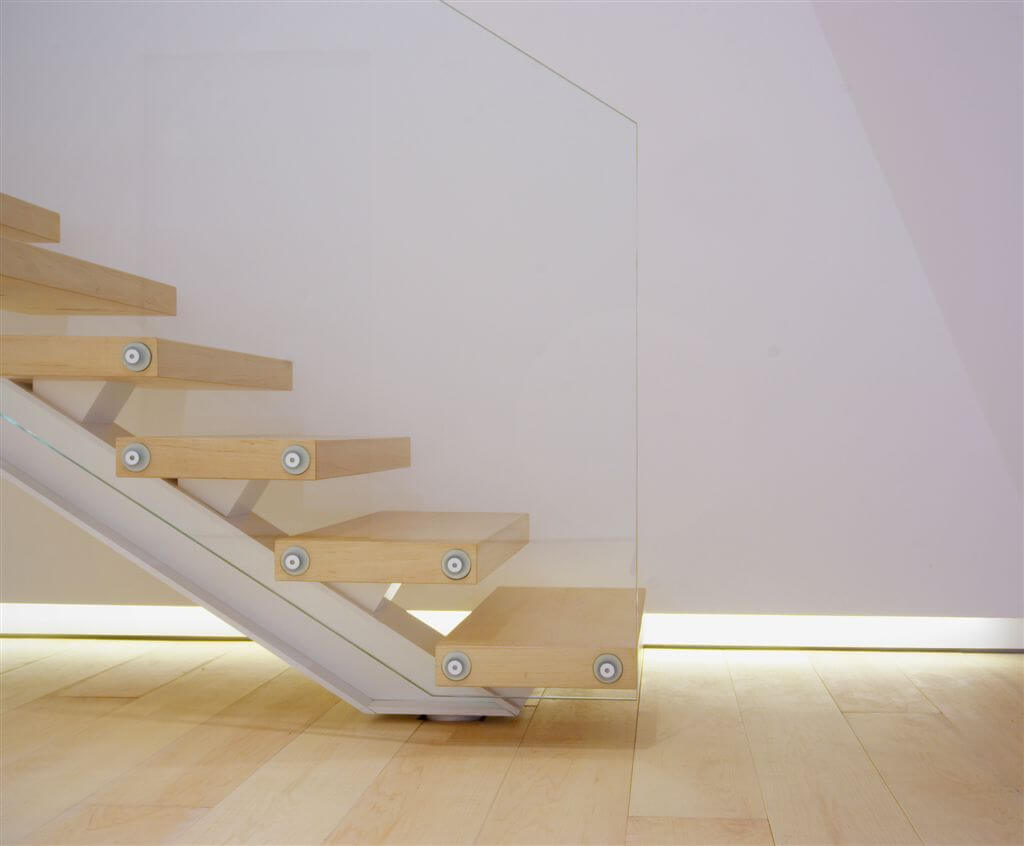 Close up view of staircase, highlighting intricate mounting and under-wall lighting.