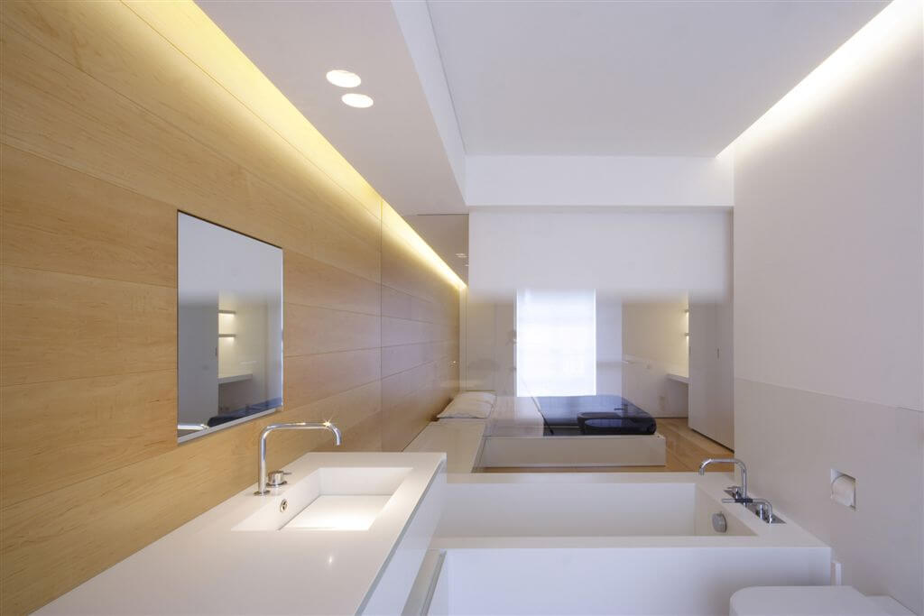 Master bathroom featuring modern minimalist sharp angles and simple white and natural wood tones. Transparent glass separates bedroom in background.