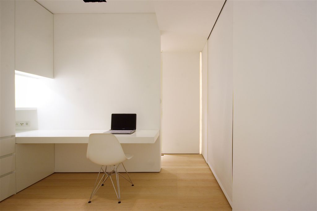 Study area with built-in desk and large white retractible curtain flush with wall.