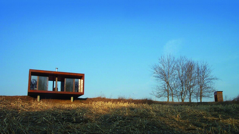 Back view of the Arado house, showcasing its compact design and all glass side overlook.