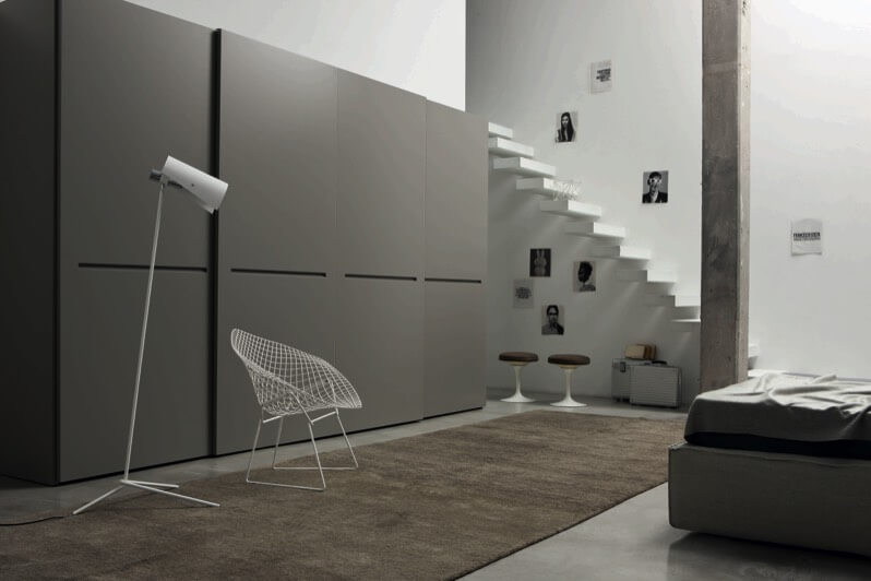 Yet again the large flush opening panels are utilized, this time in grey, in a space featuring wall-attached minimalist floating staircase and single concrete beam. Large brown area rug and brown stools accent the room behind white chair and lamp, and grey bed frame.