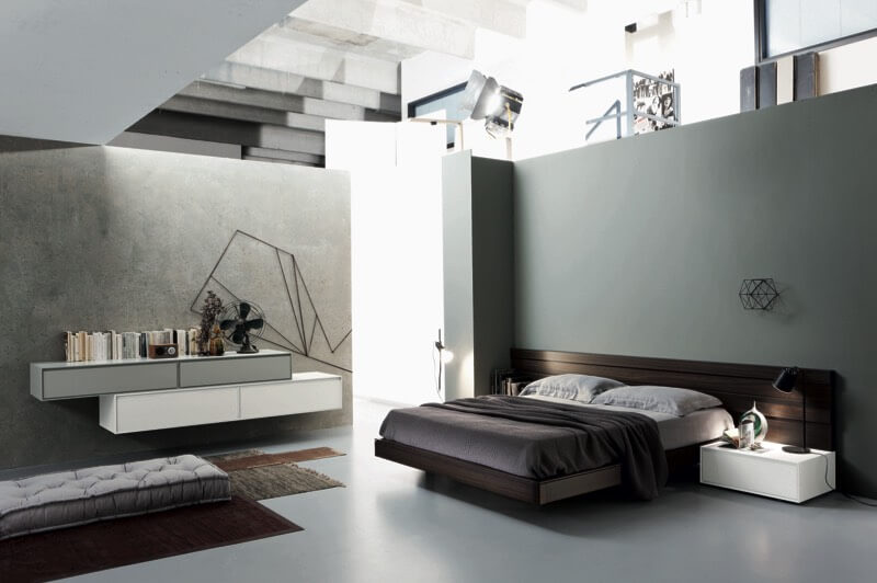This ultra modern bedroom design features minimalist grey landscape in which they've placed standout elements: dark wood bed frame and wall detail with attached white side table, cushioned floor seating over layered rugs, and tiered wall mounted shelving in white and grey.