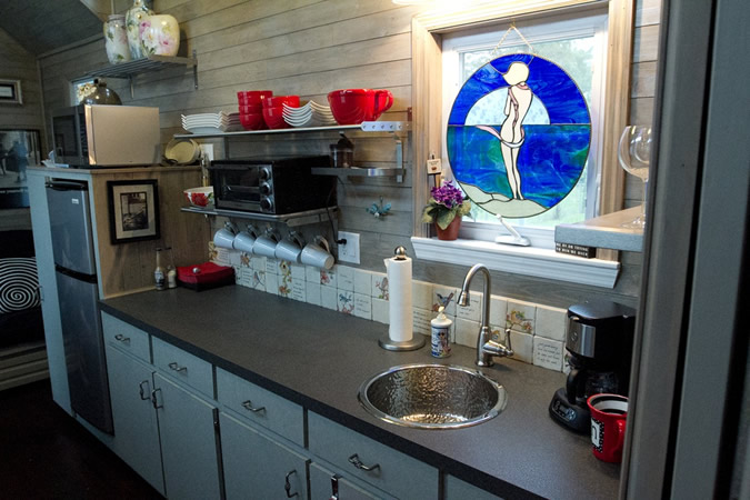 Full featured kitchen holds lengthy black countertop with sink under stained glass window cover, with appliances on left.