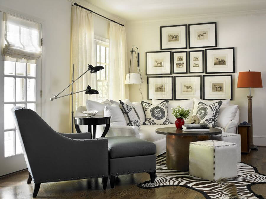 This compact white living room features dark hardwood flooring under white semi-circular sectional. Round coffee table and white cube ottomans sit on zebra rug, with grey easy chair on left.