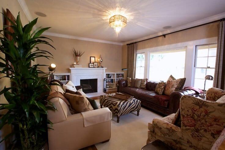 Voici un grand salon formel avec un grand canapé en cuir rouge rubis, un canapé brun clair, un fauteuil à motifs et un pouf à motif zébré avec des pieds en bois servant de table basse.  Le salon est aménagé de manière à faire face à une cheminée blanche dotée d'une étagère blanche intégrée de chaque côté