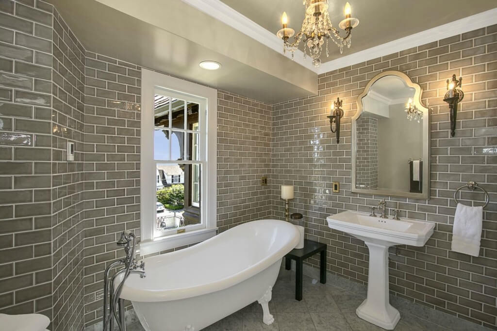 Bathroom wrapped in grey tile walls, featuring bright white claw foot pedestal tub next to vanity and window with view.