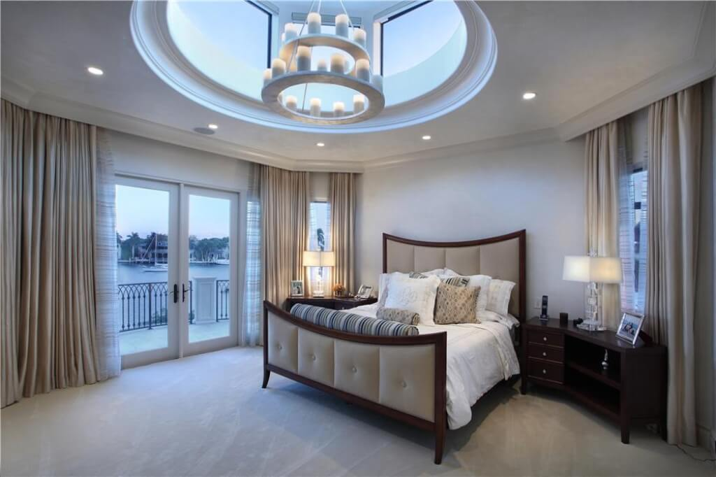 One of seven bedrooms in the home with an excellent view and an open ceiling. The bed continues the color theme of rich browns and warm beiges.
