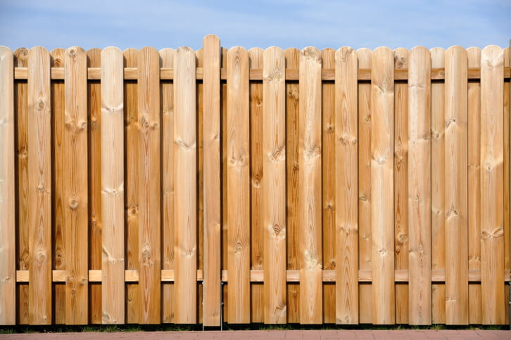 This wood fence design layers posts with rounded tops for a fully opaque look.