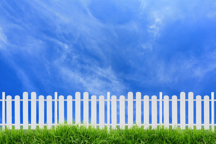 This wider gapped white fence features two slat heights, with rounded tops, between slim dividing posts.
