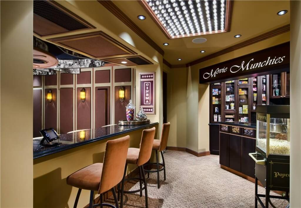 The area outside of the movie theater has darker beige walls and orange accents. Across from the bar, guests can pick up snacks before the feature film.