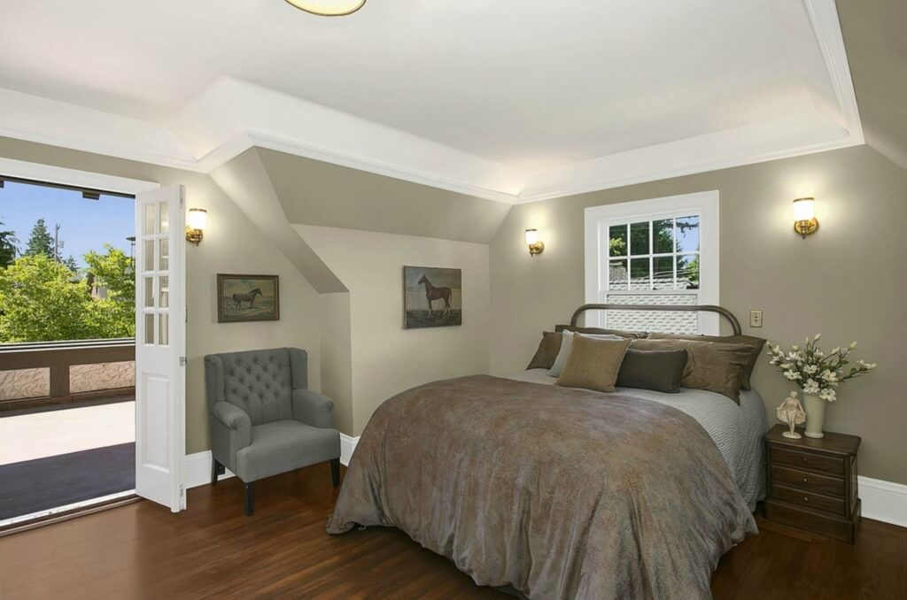 Second upper floor bedroom features hardwood flooring, dark earth tone bed, and wall sconces next to French doors to balcony.