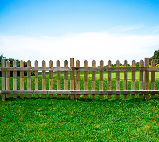 Another traditional picket fence design, this example featuring natural wood posts with angled tops.