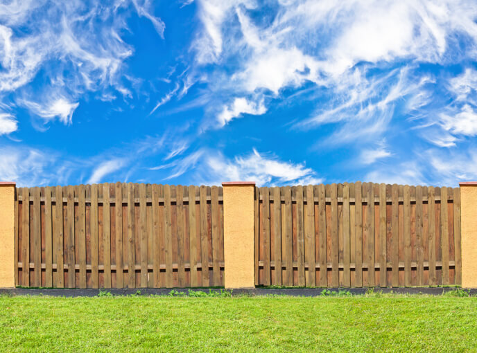 Layered privacy fence featuring darker natural wood, spaced between beige concrete pillars.